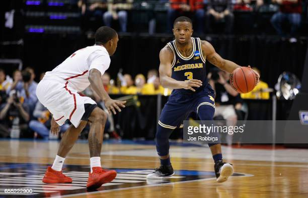 Xavier Simpson of the Michigan Wolverines drives against Tony Hicks of the Louisville Cardinals in the first half during the second round of the 2017...