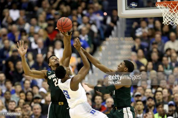 Xavier Tillman and Aaron Henry of the Michigan State Spartans defend RJ Barrett of the Duke Blue Devils in the East Regional game of the 2019 NCAA...