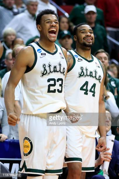 Xavier Tillman and Nick Ward of the Michigan State Spartans celebrate from the bench against the Minnesota Golden Gophers during the second half in...
