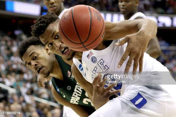 Xavier Tillman of the Michigan State Spartans and Javin DeLaurier of the Duke Blue Devils battle for the ball during the first half in the East...