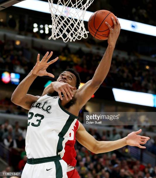 Xavier Tillman of the Michigan State Spartans attempts a shot while being guarded by Charles Thomas IV of the Wisconsin Badgers in the first half...