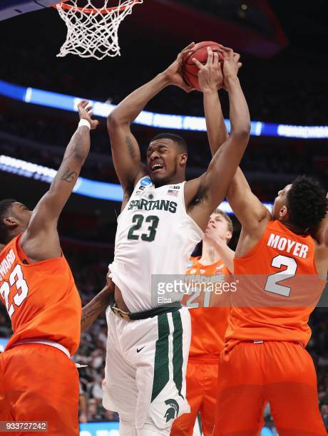 Xavier Tillman of the Michigan State Spartans battles for the ball with Frank Howard and Matthew Moyer of the Syracuse Orange during the first half...