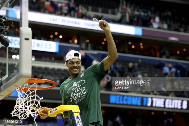 Xavier Tillman of the Michigan State Spartans celebrate by cutting down the net after defeating the Duke Blue Devils in the East Regional game of the...