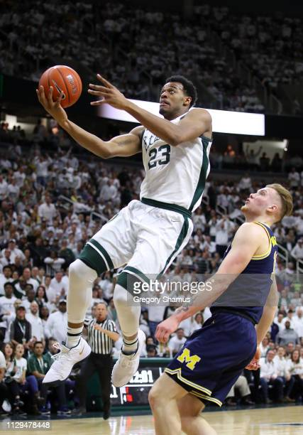 Xavier Tillman of the Michigan State Spartans drives to the basket in front of Ignas Brazdeikis of the Michigan Wolverines during the first half at...