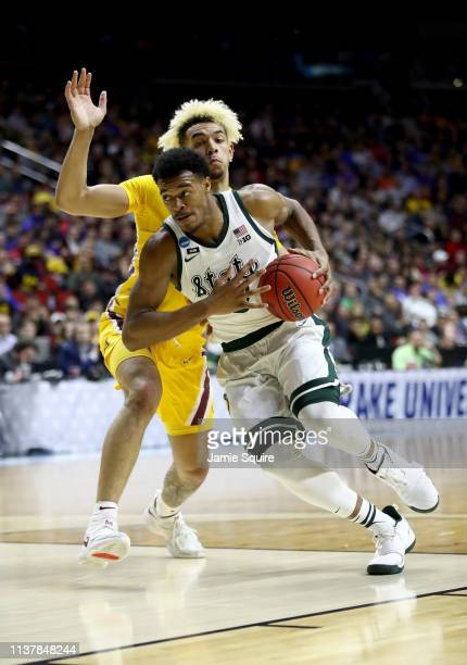 Xavier Tillman of the Michigan State Spartans drives to the basket against Jarvis Omersa of the Minnesota Golden Gophers during the first half in the...