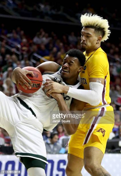Xavier Tillman of the Michigan State Spartans falls with the ball against Jarvis Omersa of the Minnesota Golden Gophers during the second half in the...
