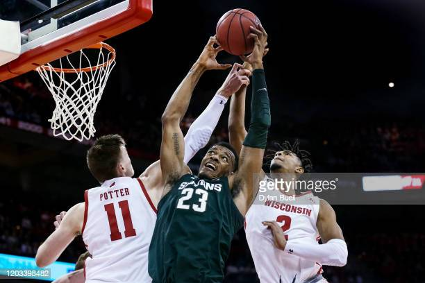 Xavier Tillman of the Michigan State Spartans grabs a rebound between Micah Potter and Aleem Ford of the Wisconsin Badgers in the first half at the...