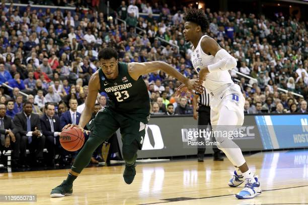 Xavier Tillman of the Michigan State Spartans is defended by Cam Reddish of the Duke Blue Devils during the first half in the East Regional game of...