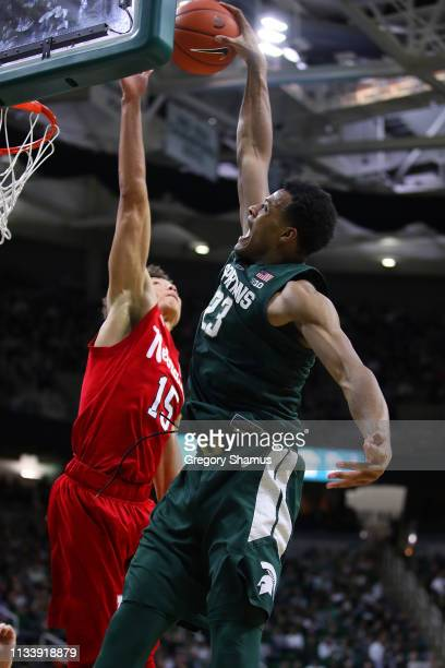 Xavier Tillman of the Michigan State Spartans tries to dunk over Isaiah Roby of the Nebraska Cornhuskers during the first half at Breslin Center on...
