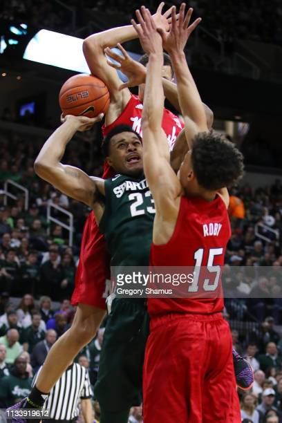 Xavier Tillman of the Michigan State Spartans tries to get a shot off over Isaiah Roby of the Nebraska Cornhuskers during the first half at Breslin...
