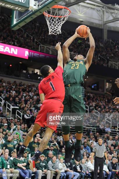 Xavier Tilman of the Michigan State Spartans shoots over Anthony Cowan Jr #1 of the Maryland Terrapins at Breslin Center on January 4 2018 in East...