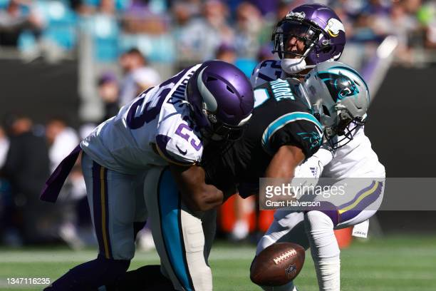Xavier Woods and Cameron Dantzler of the Minnesota Vikings knock the ball out from DJ Moore of the Carolina Panthers during the third quarter at Bank...