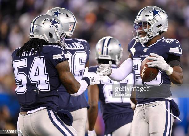Xavier Woods is congratulated by Jaylon Smith of the Dallas Cowboys after his interception during the second quarter of the game against the New York...