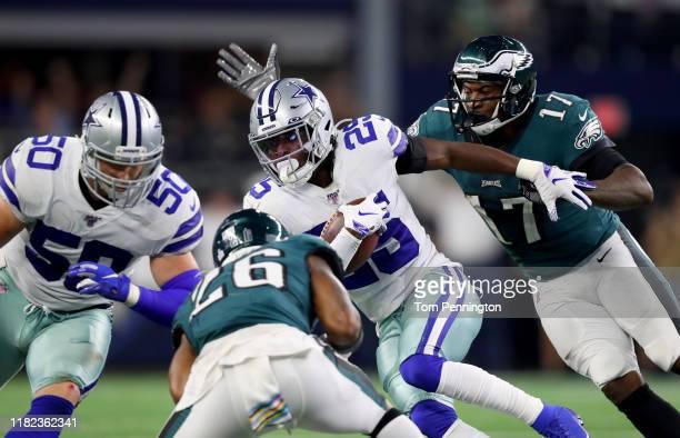 Xavier Woods of the Dallas Cowboys returns an interception against Alshon Jeffery of the Philadelphia Eagles and Miles Sanders of the Philadelphia...