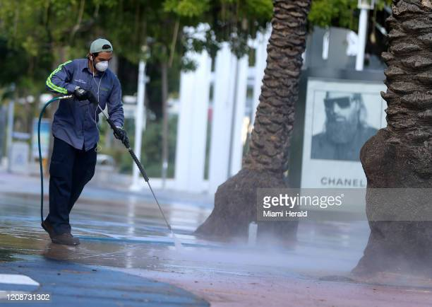 Xavier Zamora, a City of Miami Beach employee, sanitizes the sidewalks at Lincoln Road early Tuesday morning, March 31, 2020.