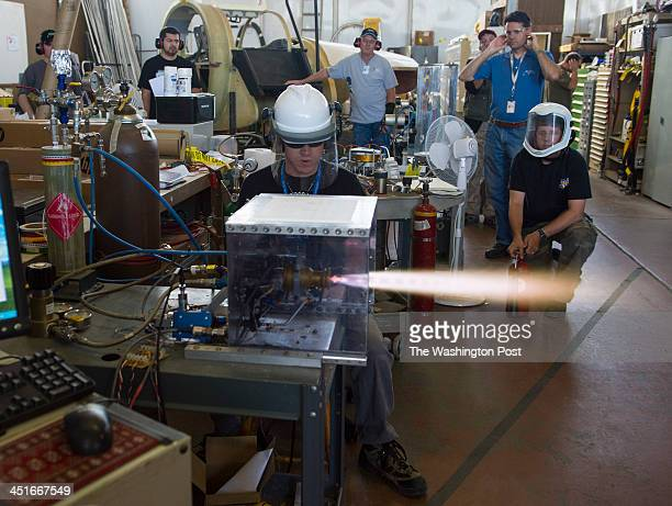 MOJAVE CA OCTOBER Xcor Aerospace test engineer Geoff Licciardello center conducts a test firing of the 3N22 RCS rocket engine has his coworkers look...