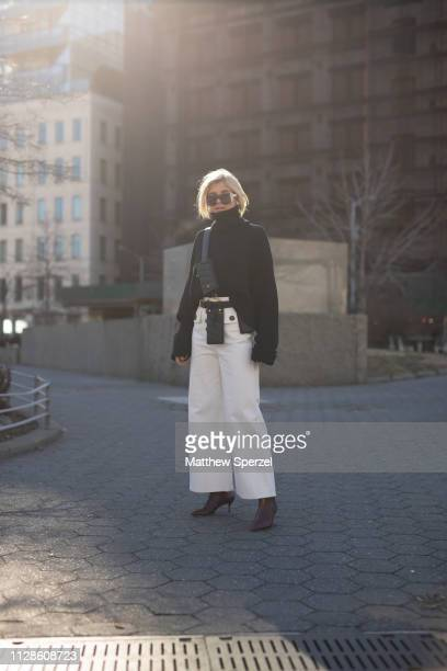 Xenia Adonts is seen on the street during New York Fashion Week AW19 wearing black sweater with white pants and leather multipocket crossbody harness...