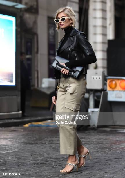 Xenia Adonts is seen wearing a black leather jacket, beige pants, black clutch and white sunglasses outside the Michael Kors show during New York...