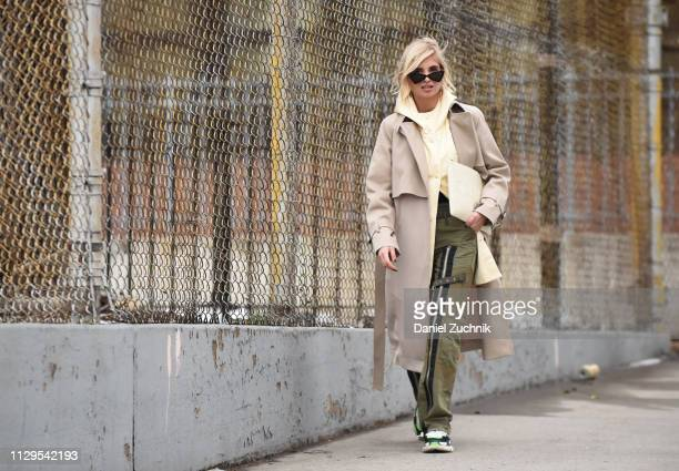 Xenia Adonts is seen wearing a Boss trench coat and Celine bag outside the Boss show during New York Fashion Week: Fall/Winter 2019 on February 13,...
