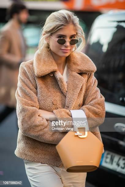 Xenia Adonts is seen wearing beige teddy jacket, Danse Lente bag outside Schiaparelli during Paris Fashion Week - Haute Couture Spring Summer 2019 on...