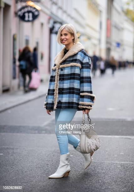 Xenia Adonts is seen wearing blue navy white plaid shearling jacket Miu Miu Fendi boots blue Acne pants black Celine blouse Loewe bag on October 20...
