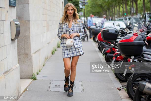 Xenia Adonts is seen wearing checkered blazer and skirt, laced boots, micro bag Dior outside Dior on July 05, 2021 in Paris, France.