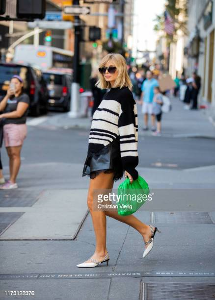 Xenia Adonts is seen wearing green clutch, black shorts, striped knit outside Self-Portrait during New York Fashion Week September 2019 on September...