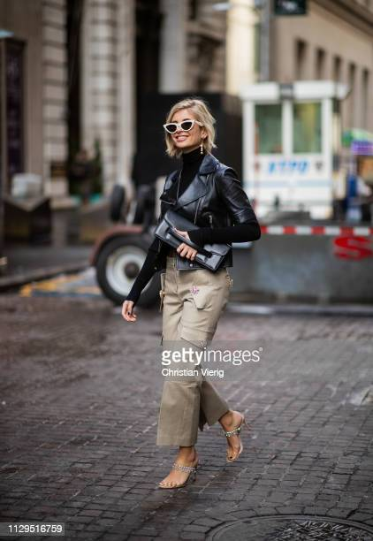 Xenia Adonts is seen wearing leather jacket beige pants cropped top outside Michael Kors during New York Fashion Week Autumn Winter 2019 on February...
