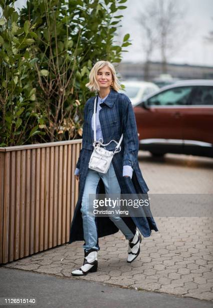 Xenia Adonts is seen wearing plaid coat, white bag, blue pants, cowboy boots outside Munthe during the Copenhagen Fashion Week Autumn/Winter 2019 -...
