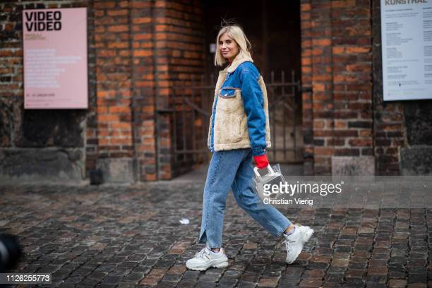 Xenia Adonts is seen wearing shearling denim jacket jeans with slit see trough bag sneaker outside Holzweiler during the Copenhagen Fashion Week...
