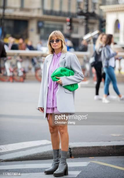 Xenia Adonts seen wearing green Bottega Veneta pouch bag pink button shirt shorts blazer outside Stella McCartney during Paris Fashion Week...