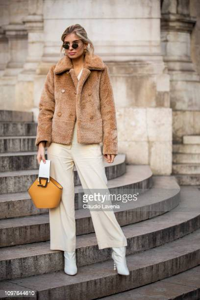 Xenia Adonts, wearing a beige fur jacket, white pants, white boots and beige bag, is seen outside Schiaparelli during Paris Fashion Week - Haute...