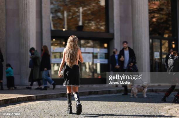 Xenia Adonts wearing a black dress and black boots outside Miu Miu Show on October 05, 2021 in Paris, France.