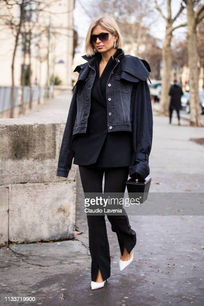 Xenia Adonts wearing a black suit white heels black bag and black denim jacket is seen outside Sacai on Day 8 Paris Fashion Week Autumn/Winter...