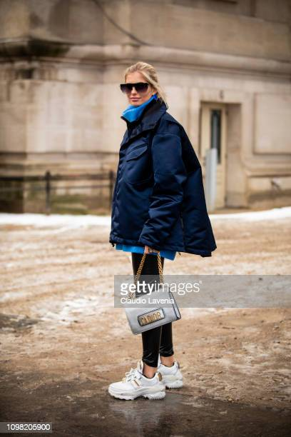 Xenia Adonts wearing a blue jumper dark blue jacket black leather pants white sneakers and silver Dior bag is seen outside Alexandre Vauthier show...