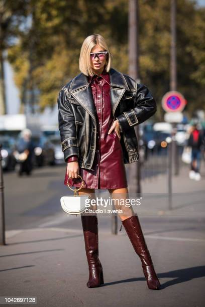 Xenia Adonts wearing a burgundy leather mini dress black leather jacket burgundy boots and white Chloe bag is seen before the Balmain show on...