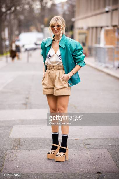 Xenia Adonts, wearing a cream shirt with decorated collar, beige shorts, teal leather jacket, black Miu Miu socks and beige sandals, is seen outside...