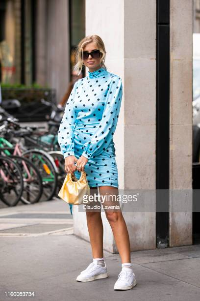 Xenia Adonts, wearing a light blue and black polka dot dress, white sneakers and yellow bag, is seen outside Schiaparelli show during Paris Fashion...