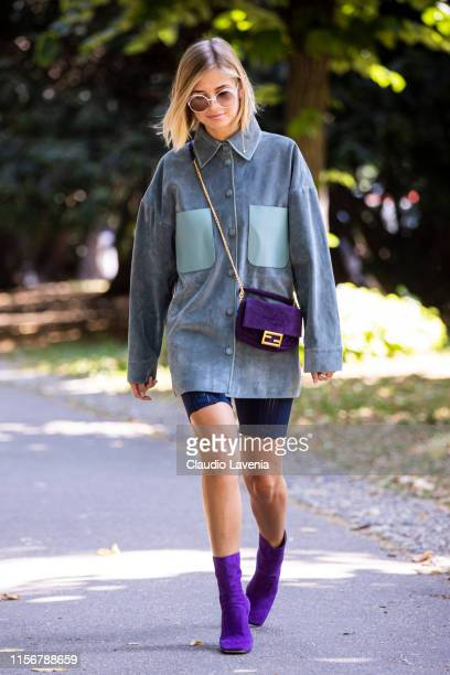 Xenia Adonts, wearing a light blue long shirt, blue biker shorts, purple boots and purple Fendi bag, is seen outside Fendi show, during the Milan...
