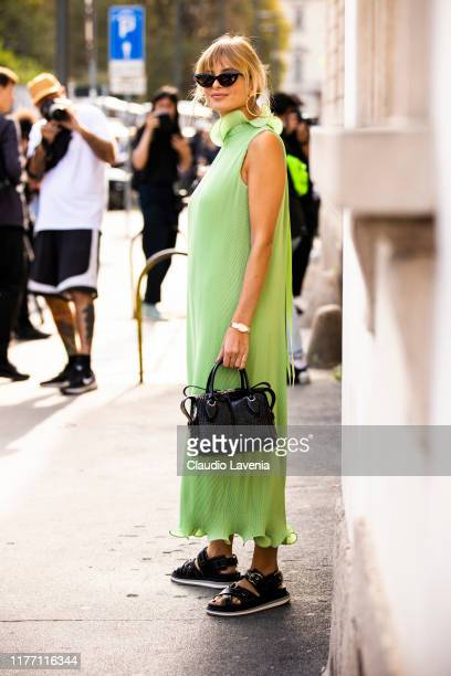 Xenia Adonts wearing a long green dress black Tod's bag and black sandals is seen outside the Tod's show during Milan Fashion Week Spring/Summer 2020...