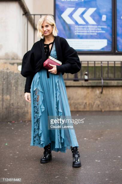 Xenia Adonts wearing a long light blue dress black boots red bag and black cardigan is seen outside Elie Saab show during Paris Fashion Week Haute...