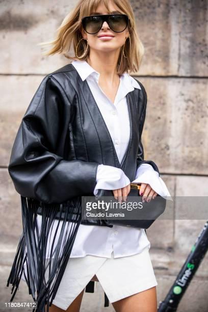 Xenia Adonts, wearing a white shirt, white mini skirt, black leather fringed jacket and black purse, is seen outside the Giambattista Valli show...