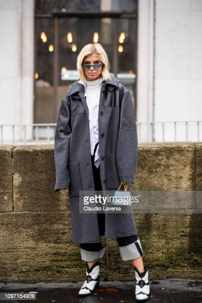 Xenia Adonts, wearing a white top, blue jeans, black and white boots, light blue Jacquemus bag and long grey coat, is seen in the streets of Paris...