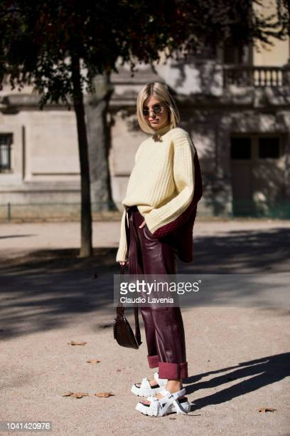 Xenia Adonts wearing a yellow and burgundy sweater burgundy trousers white sandals and burgundy fanny pack is seen after the Maison Margiela show on...