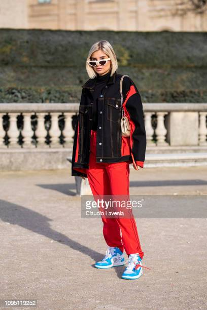 Xenia Adonts wearing black and red denim jacket red sporty pants light blue and white Nike shoes and little beige bag is seen in the streets of Paris...