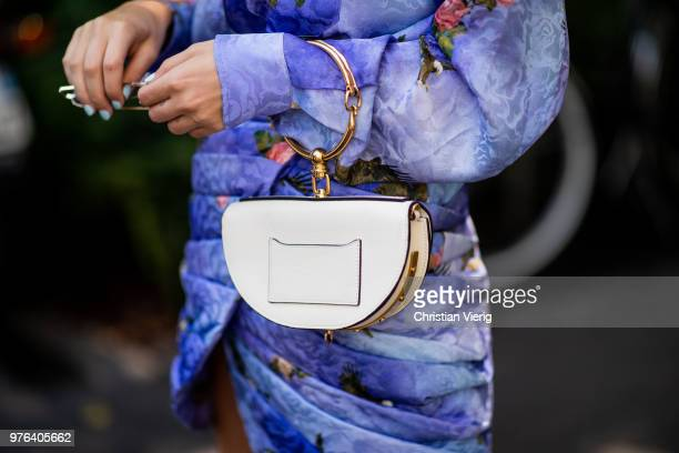 Xenia Adonts wearing blue button shirt and skirt with floral print Chloe bag is seen outside M1992 during Milan Men's Fashion Week Spring/Summer 2019...