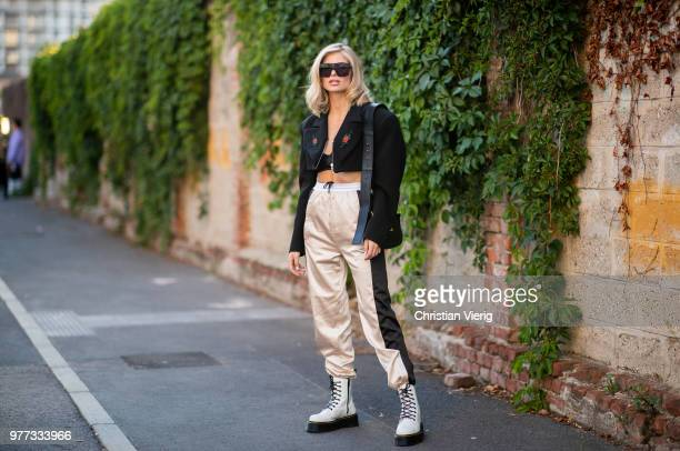 Xenia Adonts wearing boots jogger pants cropped jacket is seen outside Palm Angels during Milan Men's Fashion Week Spring/Summer 2019 on June 17 2018...