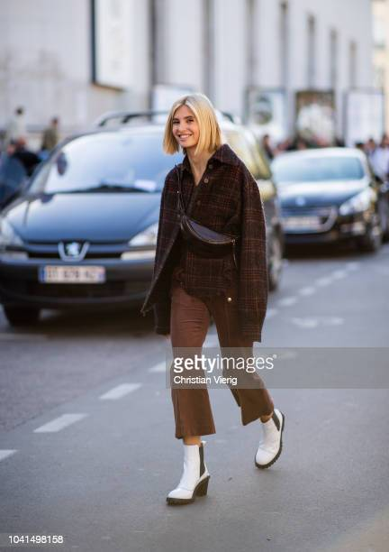 Xenia Adonts wearing brown checked jacket and cropped pants white boots is seen outside Guy Laroche during Paris Fashion Week Womenswear...