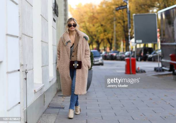 Xenia Adonts wearing Fabrizio Viti shoes jeans from RTA top Anine Bing bag is from Prada coat from Baum Pferdgarten sunglasses from Saint Laurent and...