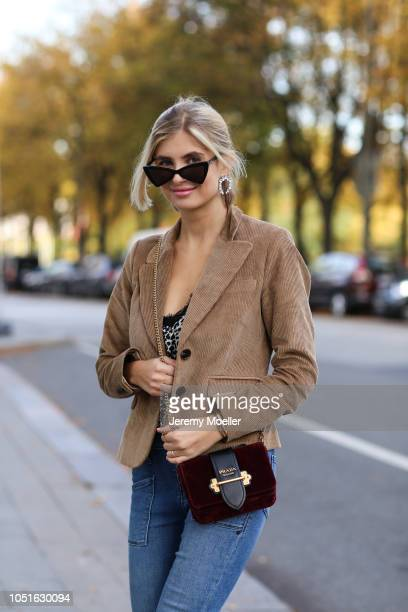 Xenia Adonts wearing Fabrizio Viti shoes jeans from RTA top Anine Bing bag is from Prada blazer from Baum Pferdgarten sunglasses from Saint Laurent...